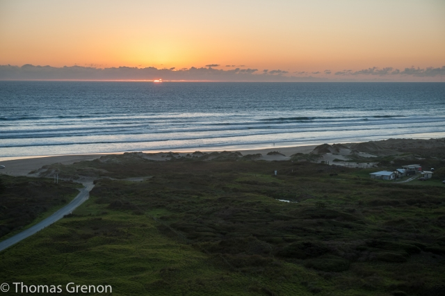 Tom climbed up Utea Hill to get some sunset shots. I'm watching from the beach, knee-deep in the Tasman Sea.